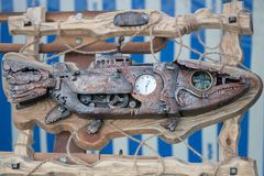 Rusty iron fish in a wooden frame wrapped with a rope, with a clock in the middle, white and blue background royalty free stock photography
