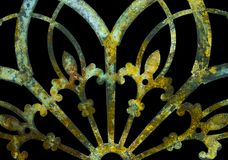 Rusty iron grunge green and yellow lacy metal decoration with fleur-de-lis isolated on black royalty free stock photography