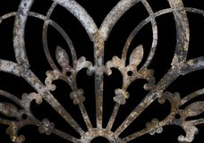 Rusty iron grunge lacy metal decoration with fleur-de-lis isolated on black. A Rusty iron grunge lacy metal decoration with fleur-de-lis isolated on black stock photography