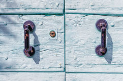 Rusty iron handles on a painted wooden door Royalty Free Stock Photo