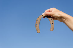 Rusty iron horseshoe in hand on blue sky bckground Royalty Free Stock Photos