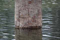 Rusty iron pillar in water stock images