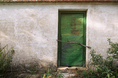 A rusty iron shed or hut painted green in the woods. Royalty Free Stock Images