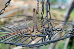 Rusty iron triple hook on grate hanging on chains Stock Images