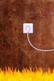 Rusty iron wall with an electrical outlet and fire Royalty Free Stock Images