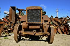 Rusty John Deere tractor by scrap iron pile Stock Photos