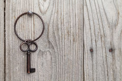 Rusty key and keyring. Hanging on a wooden background Royalty Free Stock Photography