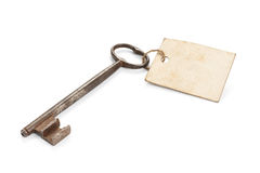 Rusty Key With Message Label. Old key with worn blank message label, isolated on white stock images