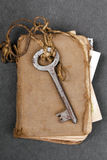 Rusty key and old book on dark background Royalty Free Stock Photo