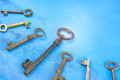 Rusty keys angle view. Old keys at an angle on blue texture Stock Photos