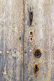 The rusty knocker and locks on a very old wooden door Royalty Free Stock Images