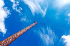 Rusty light pole from below with light cables into blue sky. A rusty light pole with Ray light cables view from below Royalty Free Stock Image