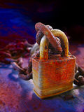 Rusty lock. A golden and red colored rusted lock with chain sitting upright on a textured intense colored table Stock Photo