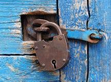 Rusty lock on a blue wooden door Stock Images