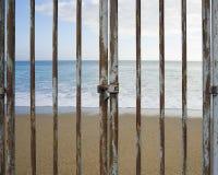 Rusty locked door with beach ocean and sky Stock Photography