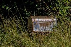 Rusty Mailbox nas ervas daninhas ao longo de uma estrada secundária fotografia de stock royalty free