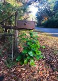 Rusty Mailbox. An old worn rusty mailbox on a country road royalty free stock photos