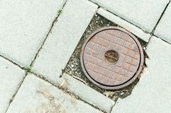 Rusty manhole cover of access point for a shut off valve to a water main along a sidewalk. Royalty Free Stock Image