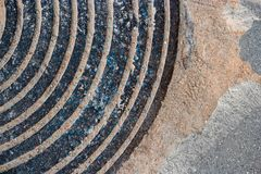 Rusty Manhole Cover Circular Pattern idoso com areia ou sujeira em The Edge foto de stock