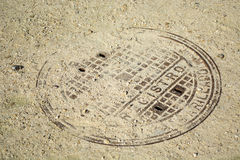 Rusty manhole cover. Detail with words in Spanish blocked by sand and pebbles Stock Photos
