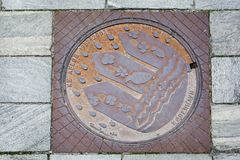 Manhole cover with natural stone pile, Copenhagen Royalty Free Stock Photo