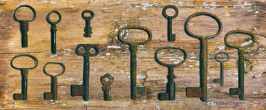 Rusty medieval keys on worn out wood table. Antique and rusty medieval castle skeleton door keys with old corroded metal ring on antique weathered barn wood Royalty Free Stock Photography