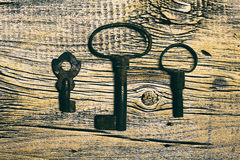 Rusty medieval keys on worn out wood table. Antique and rusty medieval castle skeleton door keys with old corroded metal ring on antique weathered barn wood Royalty Free Stock Images