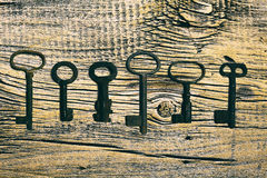 Rusty medieval keys on worn out wood table. Antique and rusty medieval castle skeleton door keys with old corroded metal ring on antique weathered barn wood Stock Photo