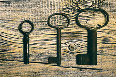 Rusty medieval keys on worn out wood table. Antique and rusty medieval castle skeleton door keys with old corroded metal ring on antique weathered barn wood Royalty Free Stock Image
