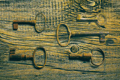 Rusty medieval keys on worn out wood table. Antique and rusty medieval castle skeleton door keys with old corroded metal ring on antique weathered barn wood Stock Photos