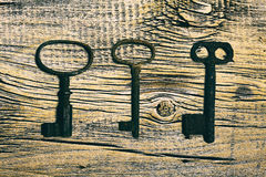 Rusty medieval keys on worn out wood table. Antique and rusty medieval castle skeleton door keys with old corroded metal ring on antique weathered barn wood Royalty Free Stock Photos