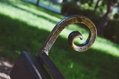 Rusty metal bench element. Rusty curly metal bench element royalty free stock image