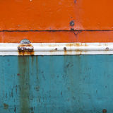 Rusty metal bow of old ship hull in orange blue and white Royalty Free Stock Photo