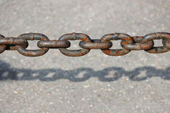 rusty metal chain hanging over the asphalt and casts a shadow. Royalty Free Stock Photography