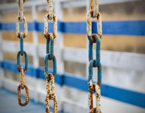 Rusty metal chain on a white and blue fence Stock Photos