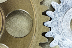 Rusty metal cogwheels on scratched brass background Stock Photos