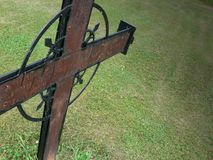 Rusty Metal Cross. Ornate, rusty metal cross against grass background stock image