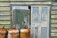 Rusty metal cylinders and weathered shed door Stock Photo