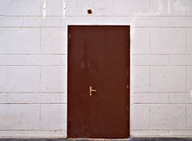 Rusty metal door in beige block wall Stock Images
