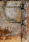 Rusty metal door details. Backgrounds and textures: rusty metal door surface with riveted hinges, industrial abstract royalty free stock photography