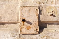 Rusty metal door of the electric box. Old abandoned electrical junction box on the wall of an old house.  stock image