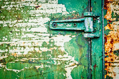 Rusty metal door with hinge cracked paint Stock Image
