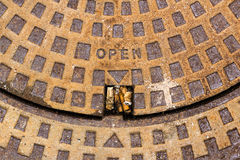 Rusty metal drain cover, with opening reference of the site. And cigarette butts inside Stock Image