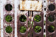 Rusty metal fence with empty name plate and summer garden. Stock Photography