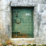 Rusty Metal Green Door on a Concrete Wall. A rustic metallic door with diamond plate patterning and two locks on a concrete wall
