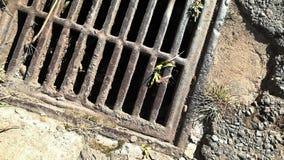 Rusty metal grill in broken asphalt from above