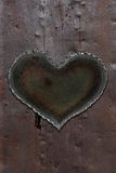 Rusty metal heart. Photo of a metal heart attached to a sheet of rusty sheet metal stock photography