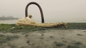 Rusty metal hook on a pier in a rope.  stock video footage