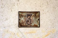 Metal house number 3 on a plastered wall. Rusty metal house number three 3 on a plastered wall Royalty Free Stock Photos