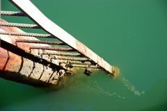 Rusty metal ladder coming out of green ocean water Royalty Free Stock Images